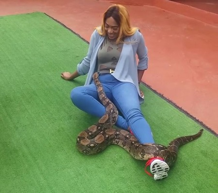 Unbelievable! Nigerian Actress Caught Playing with Lions and Romancing a Snake in South Africa (Videos)