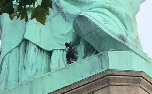 Americans In Shock As African Immigrant Climbs Statue Of Liberty To Protest Immigration Policy (Photos)