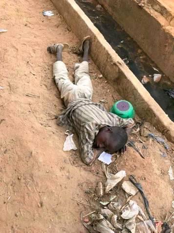 Almajiri boy sleeping on a pile of dirt