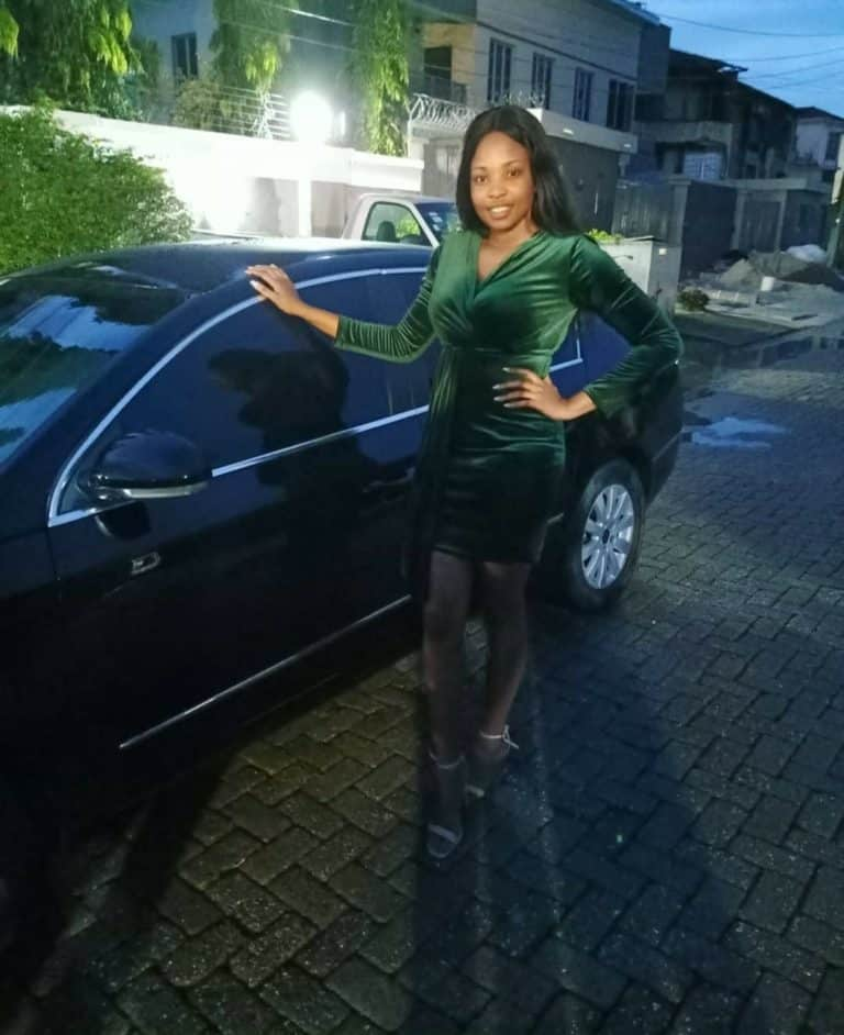 Cindy Okafor poses in front of her car