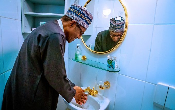 Buhari washing hands with gold-plated tap