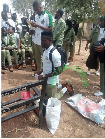 NYSC member kneeling as punishment