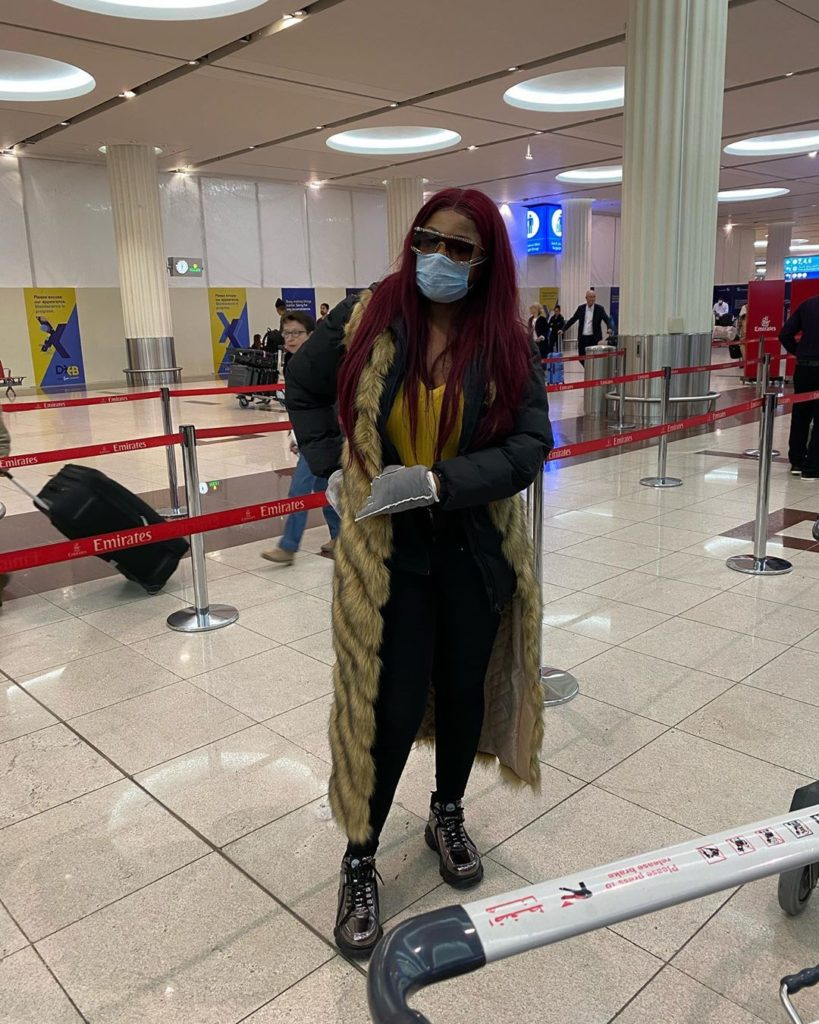 Tacha posing for photo at the airport