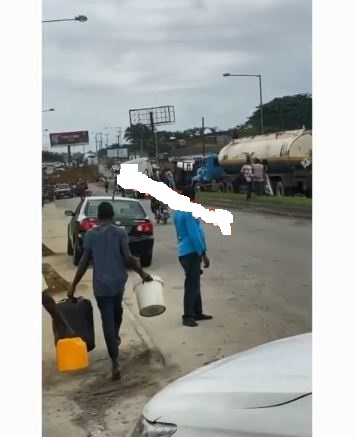 People scooping fuel from faulty tanker