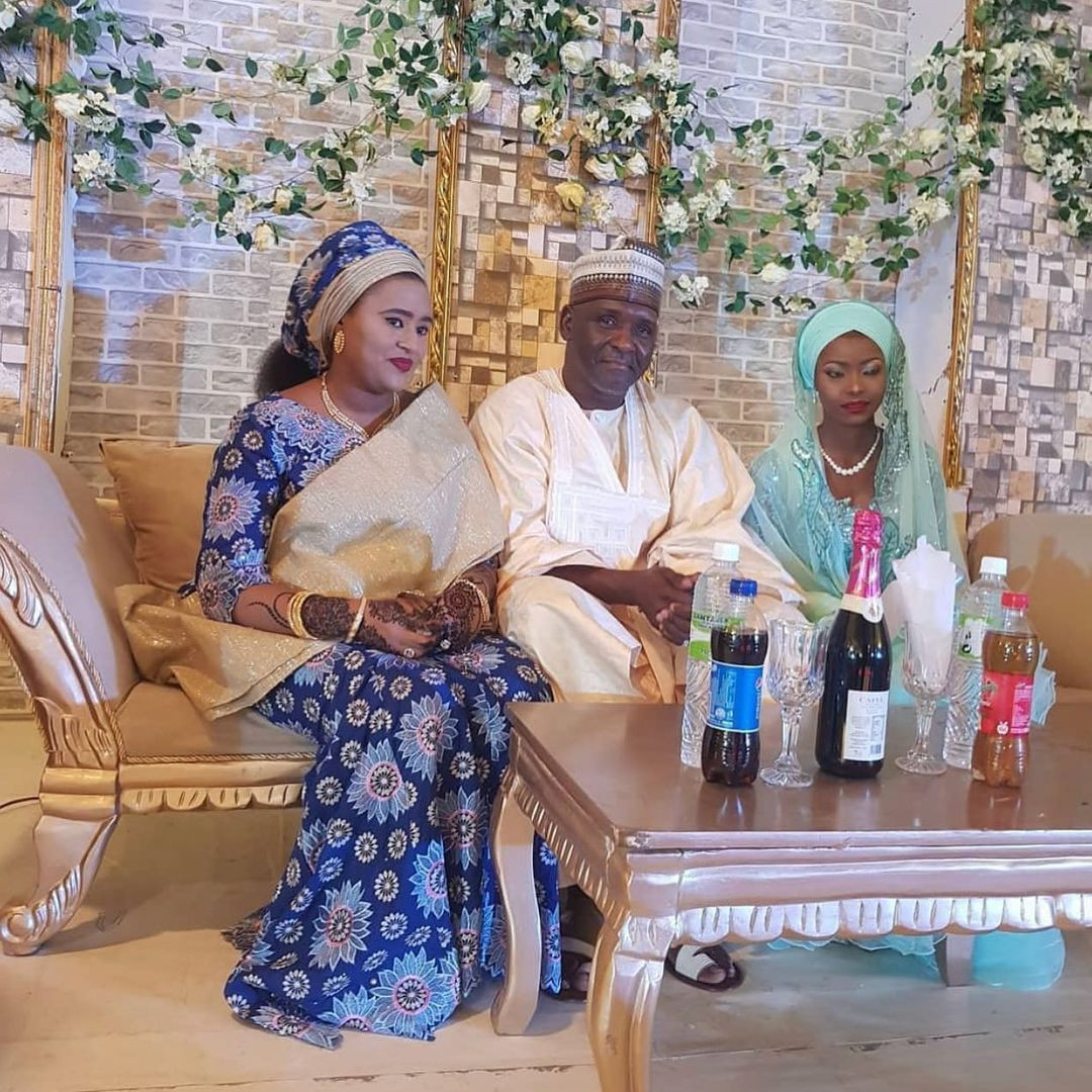 First wife posing with husband and his new wife