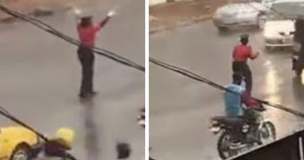 Warden controlling traffic in the rain