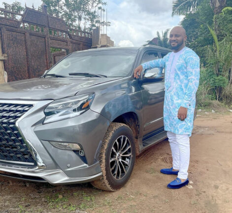 Yul Edochie posing with his brand new car